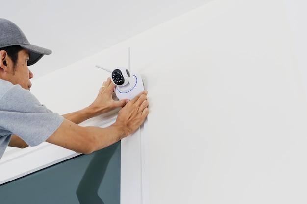 Technici installeren een draadloze cctv-camera aan de muur.