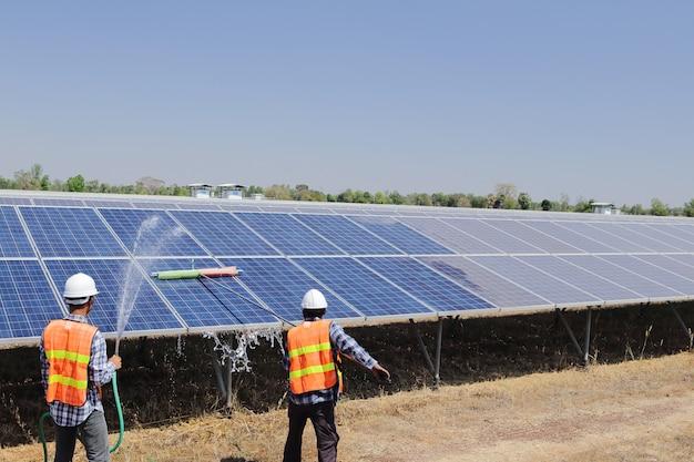 Technici om zonnecellen in een zonnecentrale te reinigen