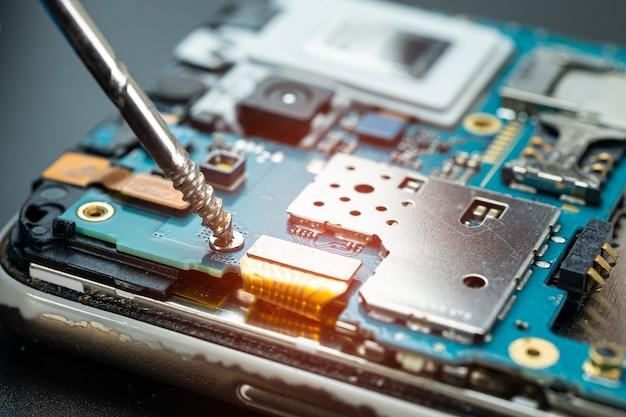 Technicus binnenkant van mobiele telefoon repareren door soldeerbout.