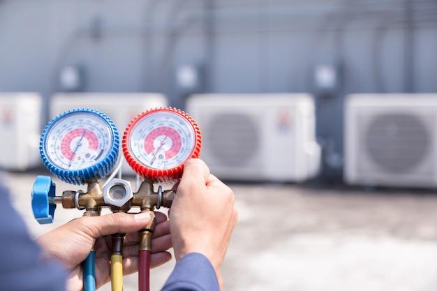 Technicus controleert airconditioner, meetapparatuur voor het vullen van airconditioners.