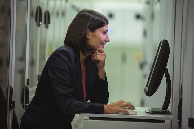 Technicus die aan personal computer werkt terwijl het analyseren van server