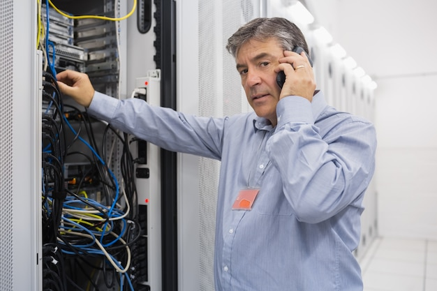 Technicus die aan server en het telefoneren werkt