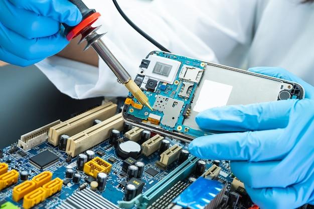 Technicus die binnenkant van harde schijf herstelt door ijzer te solderen.