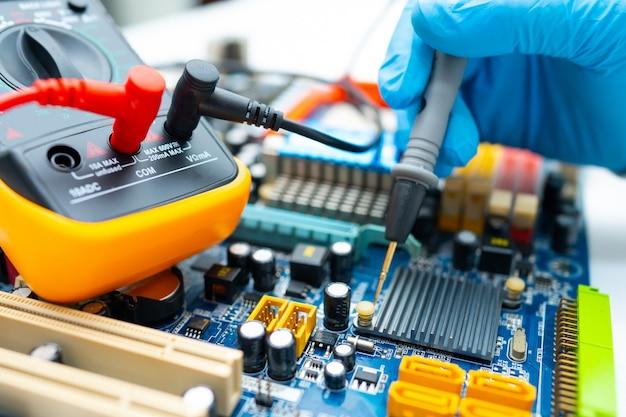 Technicus die binnenkant van harde schijf herstelt door multimeter en soldeerbout.