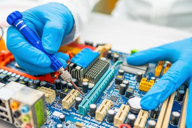 Technicus die binnenkant van harde schijf herstelt door soldeerbout.