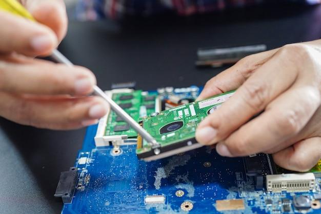 Technicus die binnenkant van harde schijfcomputer herstelt.