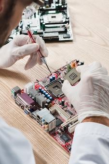 Technicus die computer-chip in motherboard op houten bureau opneemt