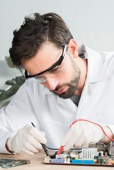 Technicus die computermotherboard met digitale multimeter onderzoeken