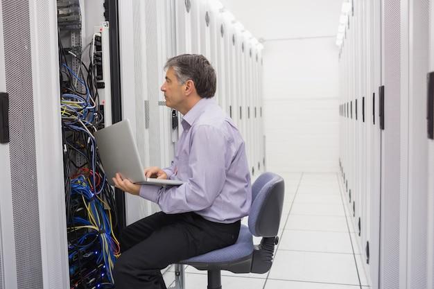 Technicus die de server met laptop controleert