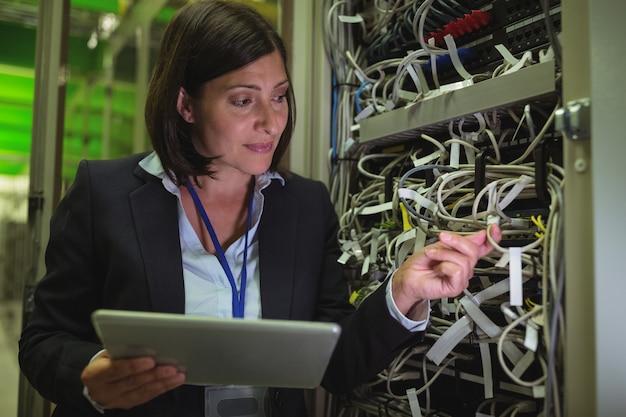 Technicus die digitale tablet gebruiken terwijl het analyseren van server
