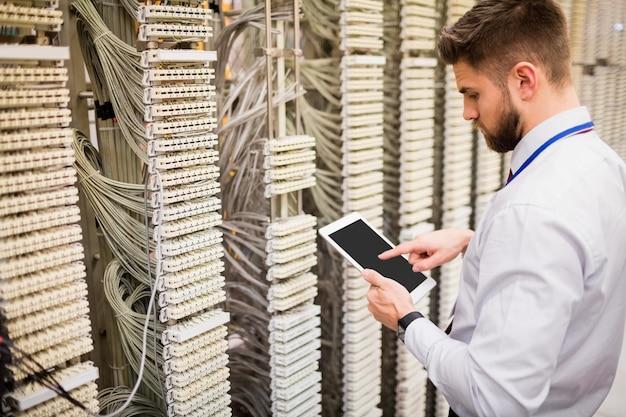 Technicus die digitale tablet gebruikt terwijl het analyseren van server
