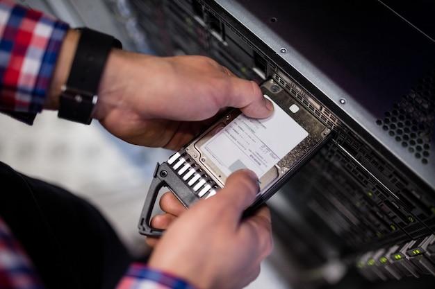 Technicus die een harde schijf in een bladserver plaatst
