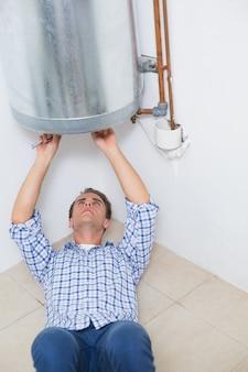 Technicus die een warm waterverwarmer onderhouden