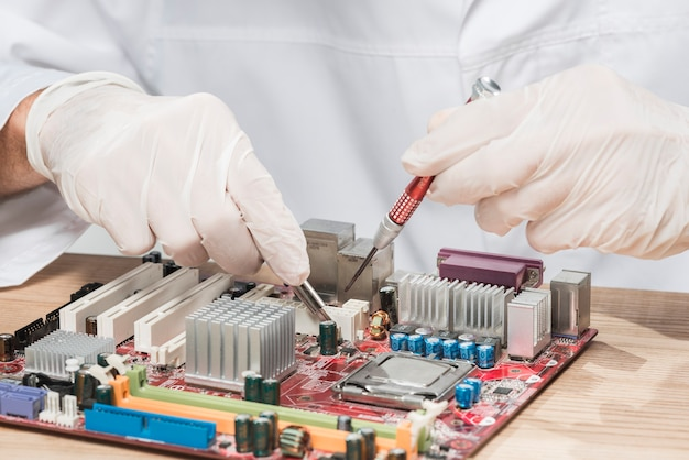 Technicus die handschoenen draagt die aan computermotherboard werken