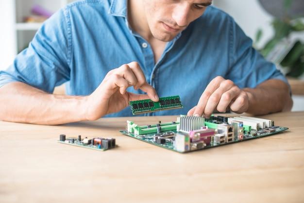 Technicus die het ram-geheugen op de aansluiting van het moederbord van de computer plaatst