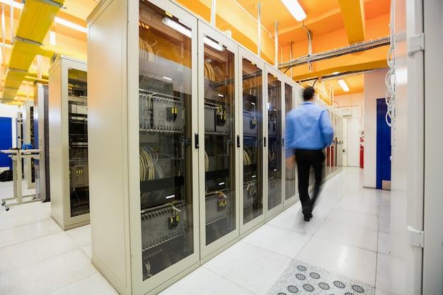 Technicus die in serverruimte loopt