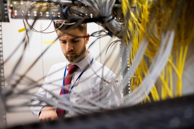 Technicus die kabels in een in een rek gemonteerde server controleert