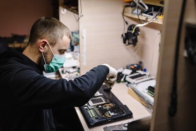 Technicus die laptop in het laboratorium herstelt. concept reparatie elektronische computer, upgrade, technologie. coronavirus. man aan het werk, het dragen van een beschermend masker in de werkplaats.