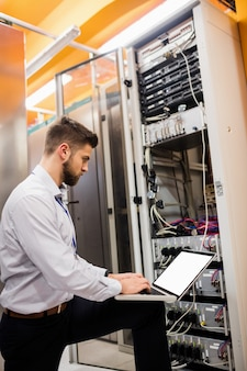 Technicus die laptop met behulp van terwijl het analyseren van server