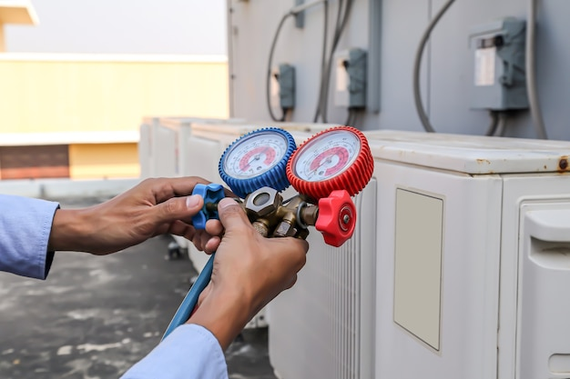 Technicus die manometer gebruikt om industriële fabrieksairconditioners voor buiten te vullen.