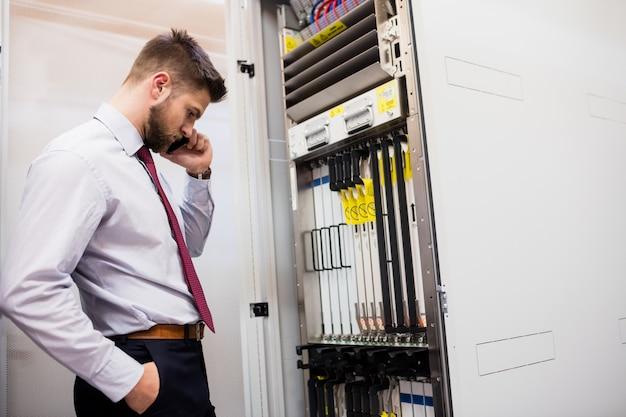 Technicus die op mobiele telefoon in serverruimte spreekt