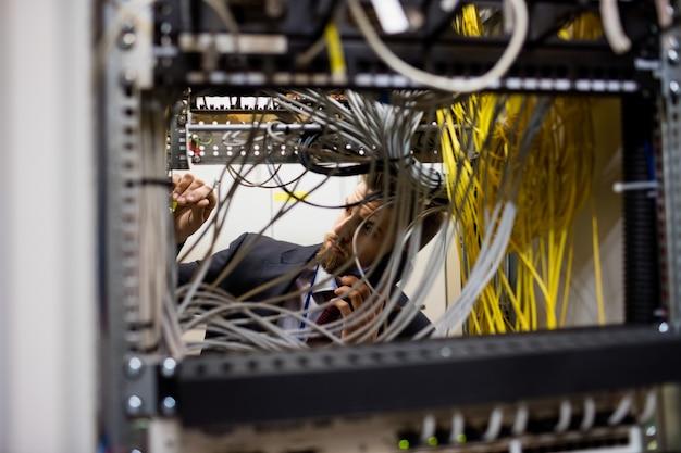Technicus die op mobiele telefoon spreekt terwijl het controleren van kabels