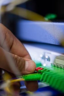 Technicus die patchkabel in een rek gemonteerde server steekt