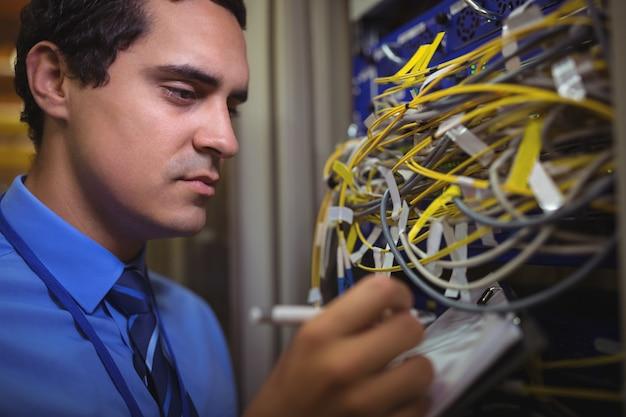Technicus die verslag van in een rek gemonteerde server op klembord bijhoudt