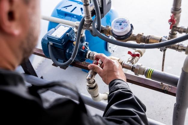 Technicus die watersysteemknopen controleert.