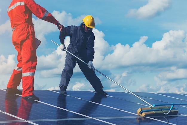 Technicus die zonnepanelen op generatorvermogen bedient en schoonmaakt