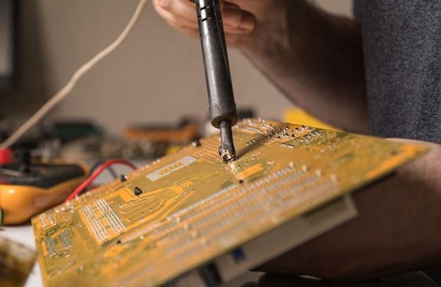 Technicus elektronisch solderen en repareren van computerchips