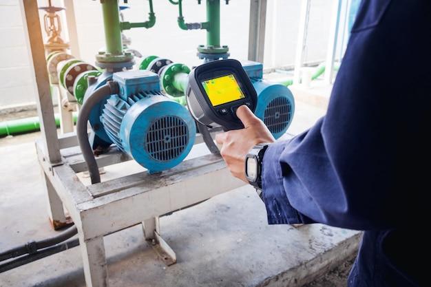 Technicus gebruikt warmtebeeldcamera om de temperatuur in de fabriek te controleren