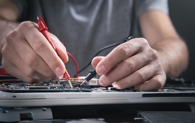 Technicus handen controleren moederbord met multimeter.