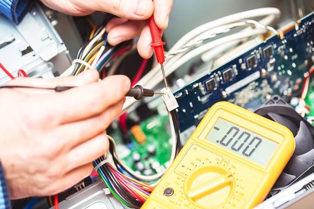 Technicus handen met voltmeter boven computer moederbord,