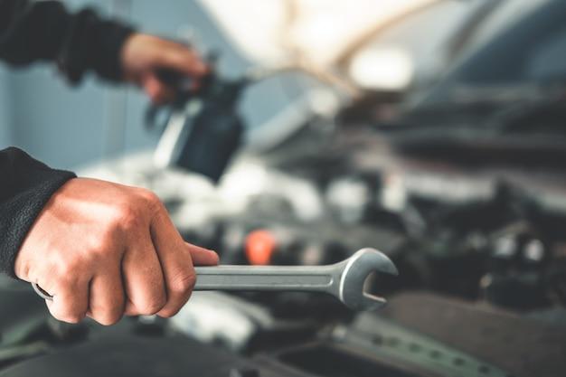 Technicus handen van automonteur die in autoreparatie werkt