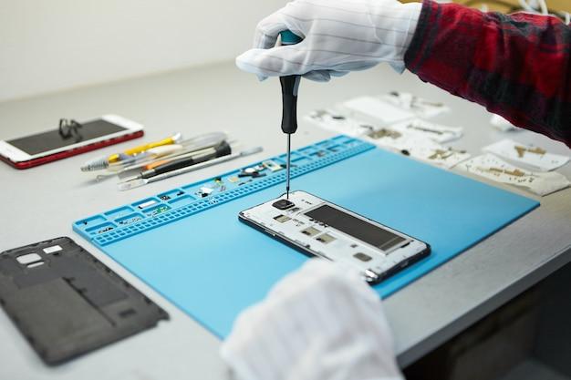 Technicus in antistatische handschoenen met schroevendraaier om borken mobiele telefoon te demonteren, moederbord te repareren, zittend op zijn werkplek in laboratorium met benodigde apparatuur