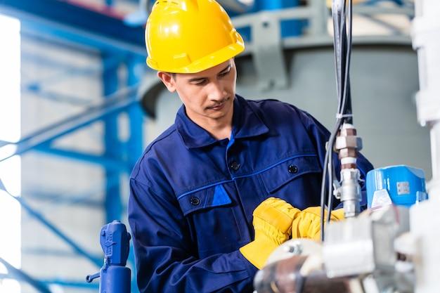 Technicus in aziatische fabriek bij machineonderhoud werken met moersleutel