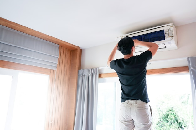 Technicus man repareren, schoonmaken en onderhoud air conditioner