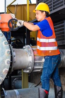 Technicus of ingenieur die aan een klep werkt bij het bouwen van technische apparatuur of een industriële site in de fabriek of het hulpprogramma