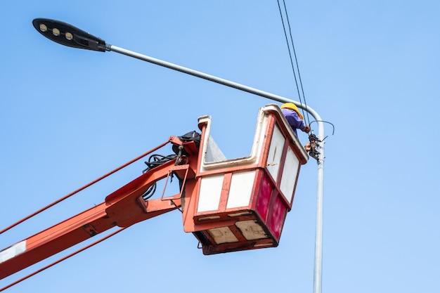 Technicus op emmervrachtwagen hoog omhoog van een kraan om straatlantaarn te bevestigen.