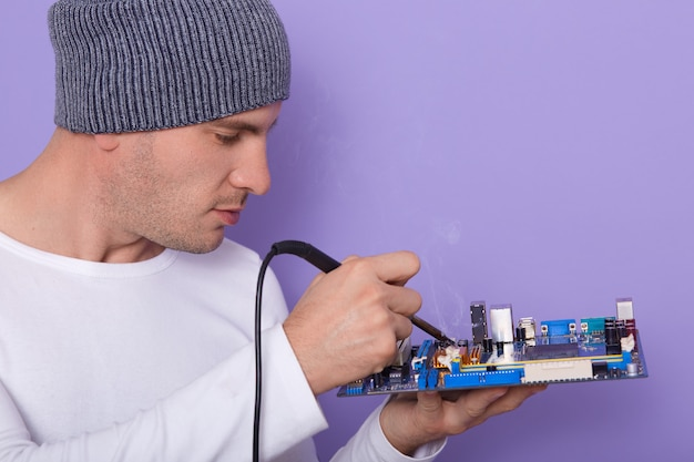 Technicus reparatie defect onderdeel van in elektronische technologie service. zijaanzicht van jonge knappe computer rapair tovenaar die grijze glb en wit overhemd dragen, hersteller die defect moederbord solderen.