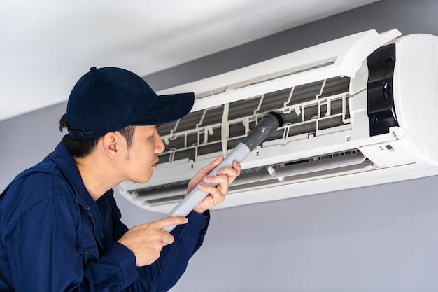 Technicus service met behulp van stofzuiger om de airconditioner te reinigen