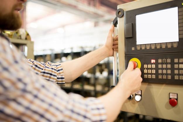 Technicus staan voor het configuratiescherm en weergeven op de muur van de industriële machine in de werkplaats en op de rode knop te drukken