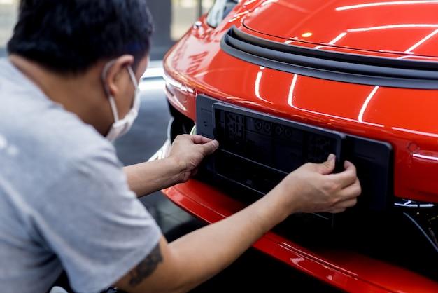 Technicus veranderend autoplaatnummer in het servicecentrum.