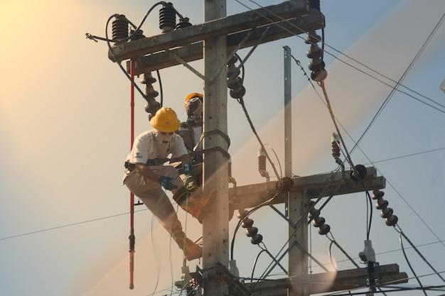 Technicus werkt op hoogspanningselektriciteitspool en reflecteert licht