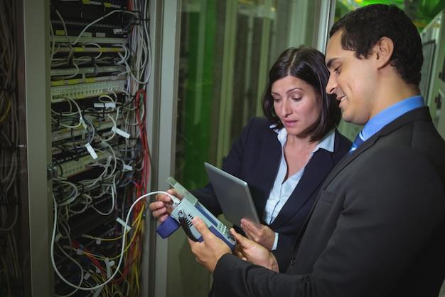 Technicus werkt op personal computer tijdens het analyseren van server technici die digitale kabelanalyses gebruiken