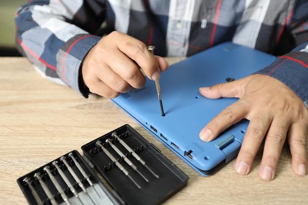 Technicusmens die schroevedraaier gebruiken om laptop computer te bevestigen of te verbeteren