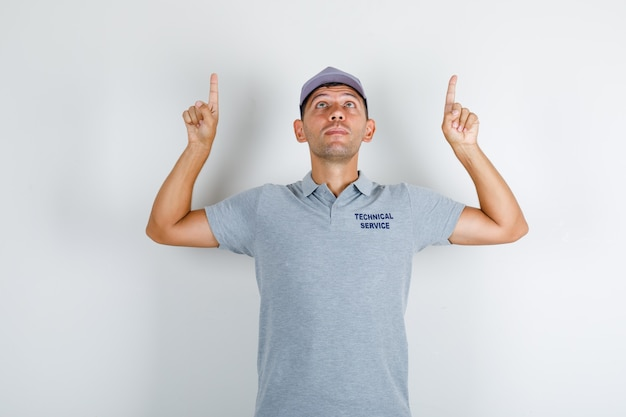 Technische dienst man in grijs t-shirt met pet die vingers omhoog wijst