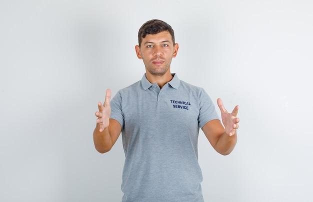 Technische dienst man in grijs t-shirt probeert iets vast te houden en kijkt blij