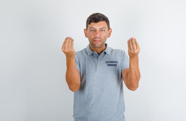 Technische dienst man italiaans gebaar doen met handen in grijs t-shirt en op zoek zelfverzekerd